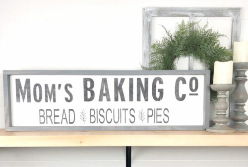 horizontal sign in white and grey with text Mo's Baking Co. Bread Biscuits Pies in text with gray frame on a shelf with candle, wreath and frame behind sign