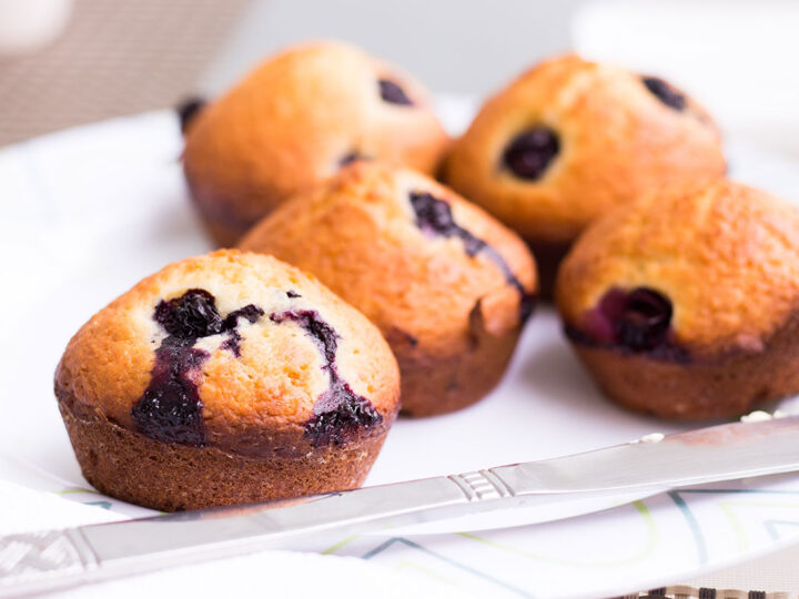 five blueberry muffins on a white napkin with knife