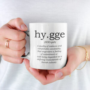 hands holding a mug with the definition of hygge printed on it