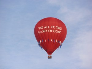 """http://YouDeserveGod.com Image is a Red Hot Air Ballon That Is Floating In The Air. On the Hot Air Balloon There Are The Words """"Do All In The Glory Of God"""""""