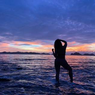 silhouette of jenny chu on a sandbar in between delepeldet island and las cabanas beach in el nido philippines during sunset