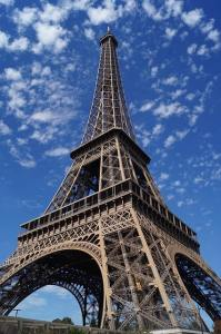 Ground view of Eiffel tower with blue skies and a few clouds.