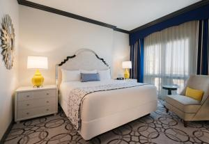 Paris Las Vegas Room with white bed and chair.