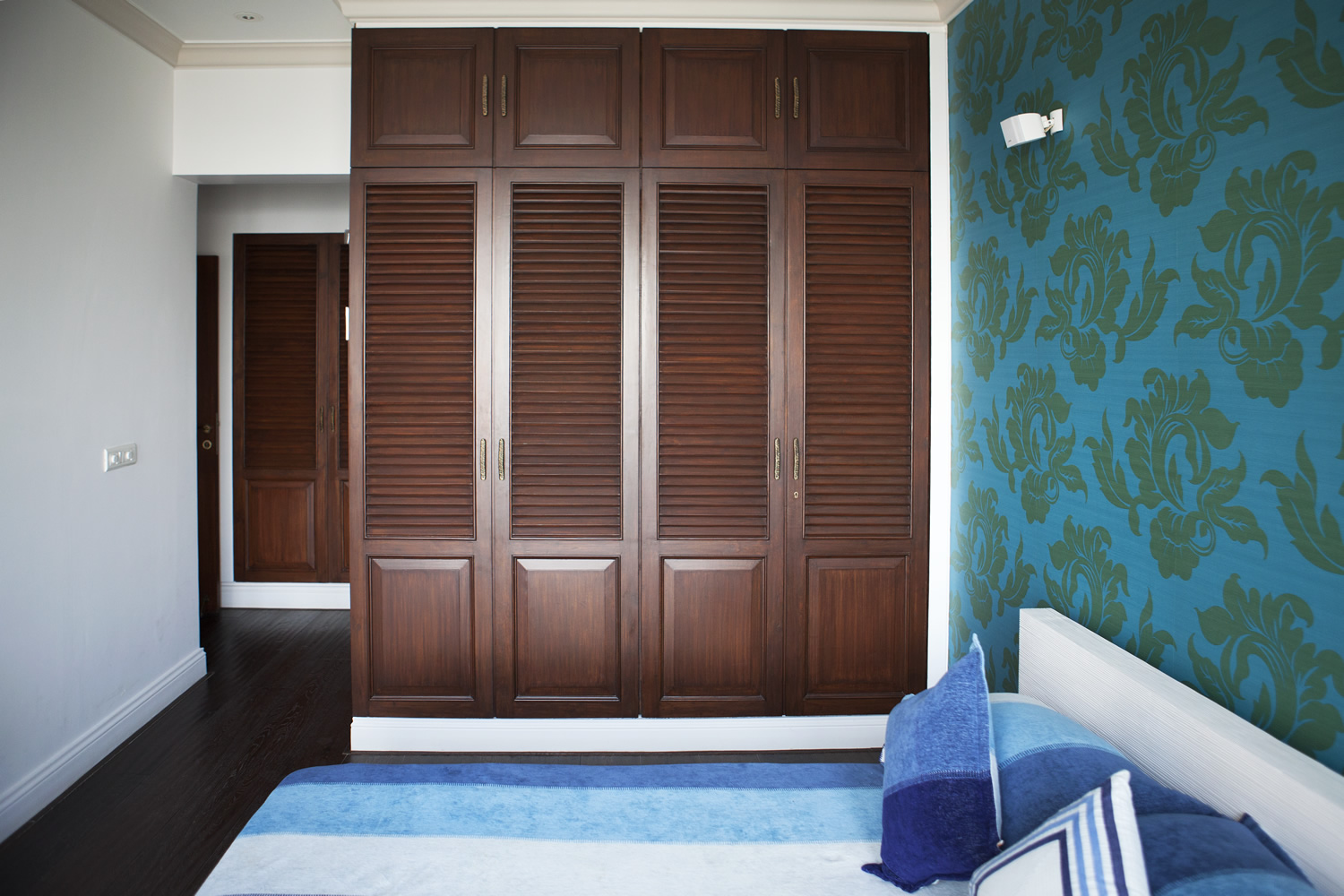 Indian bedroom furniture designs - The Beautiful Blue Flower Design Wallpaper Looks Great With The Simple Old Design Of Wardrobes The Wardrobes Of The Bedroom Are Look So Beautiful That We