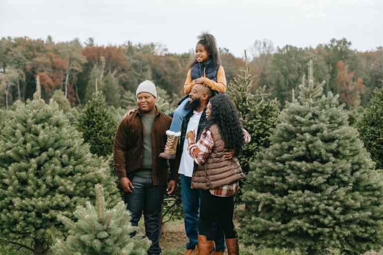 positive black family preparing for christmas on tree farm