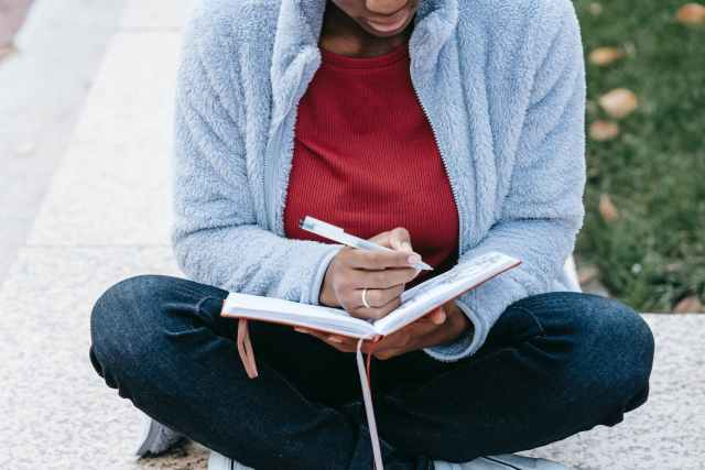crop black student with diary studying in town
