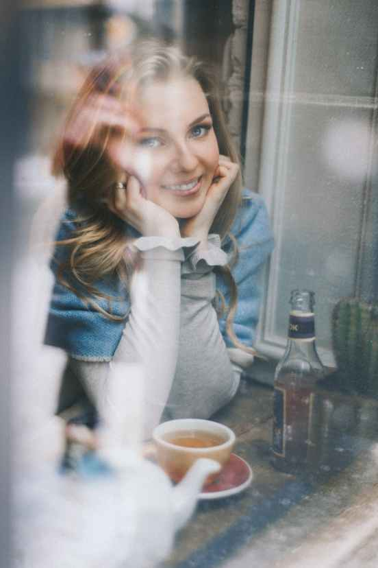 smiling woman with cup of tea at home