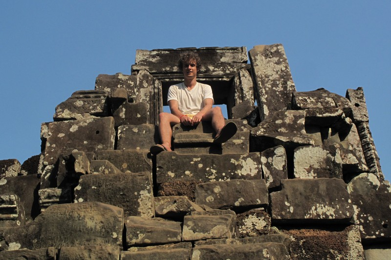 Man sitting on temple at Angkor Thom