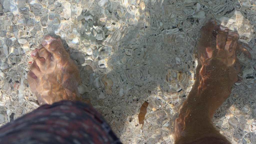 Feet in clear sea water
