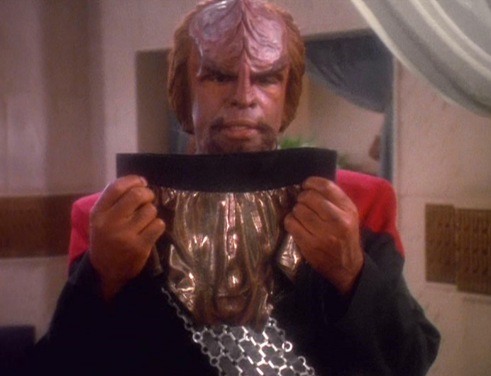 Worf from Star Trek holding up a swimsuit in disgust.