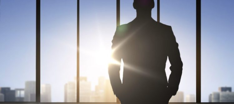silhouette of business man over office background