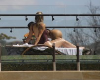 Kim and Khloe Kardashian relax poolside on their Costa Rican vacation. Kim wore a nude bikini while Khloe opted for a burgundy one-piece. Kris was also seen walking around the luxury property the family have rented.