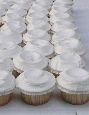 rows of white Ukrop's cupcakes at diy backyard garden wedding