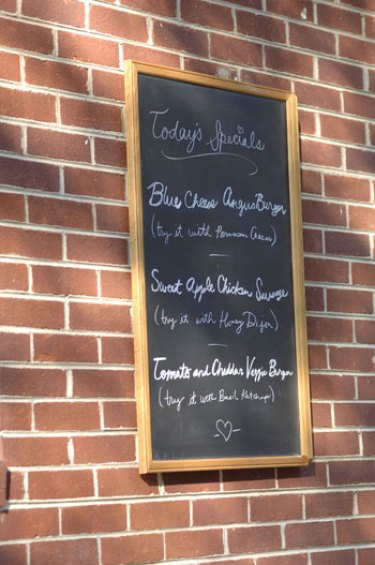 chalkboard menu hung on brick wall at backyard garden wedding