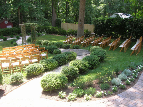 Wood Chairs Set Up In Backyard For Wedding Ceremony Around Pergola And  Pathway
