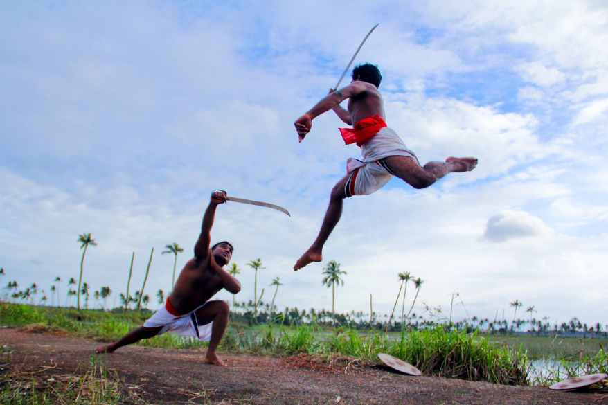 two man in white shorts fighting using sword during daytime