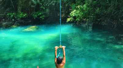 photo of boy swinging over body of water