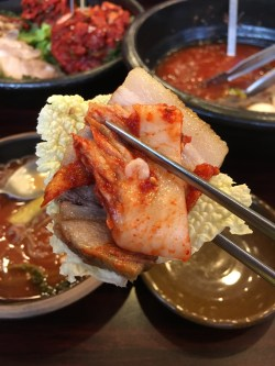 Boiled pork belly that you eat wrapped in cabbage, kimchi, pickled radish, shrimp sauce, etc.