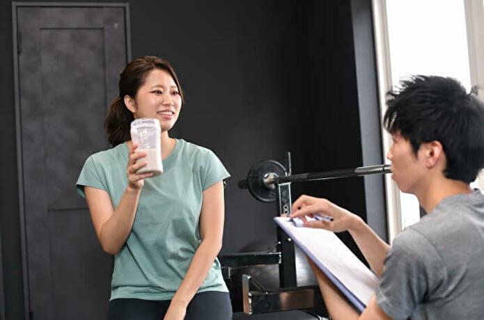 プロテインを飲み会話する女性