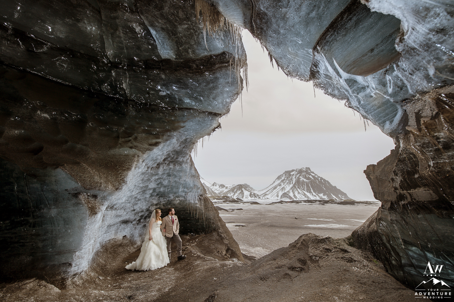 Couple Standing inside of an ice cave during Iceland wedding day adventure