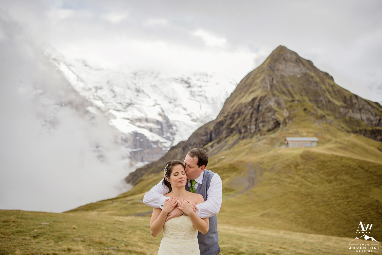 Groom Kissing his bride on Männlichen in Switzerland