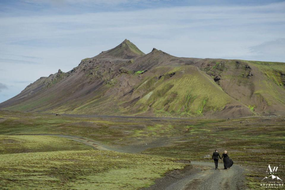 Black Dress Bride walking down a mountain road in Iceland
