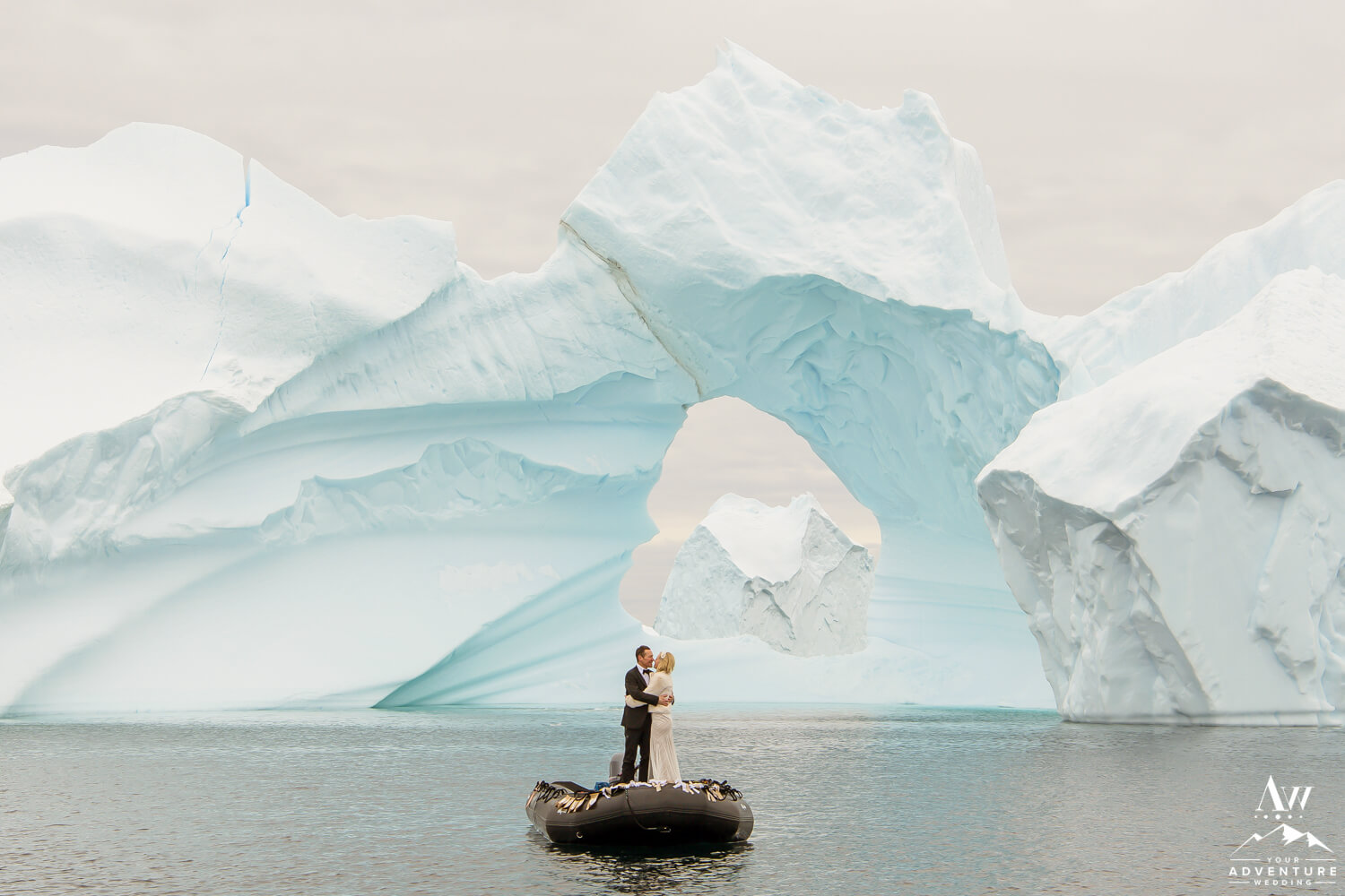 Couple Kissing in front of an Antarctica Iceberg