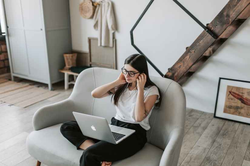 positive woman using earphones and laptop at home to listen to therapy lectures and recordings