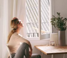 woman sitting on a chair next to a window because of ADHD