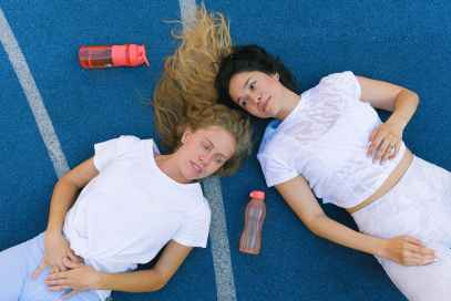 young female athletes having break during workout in sport club