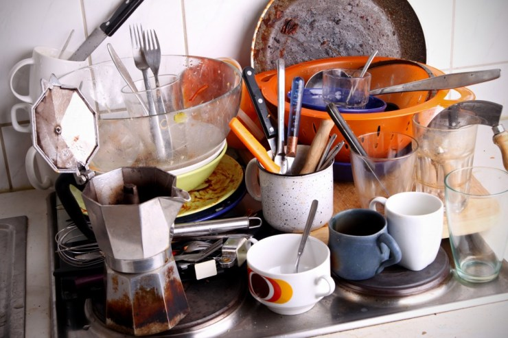 This is a ton of dishes sitting in the kitchen sink.