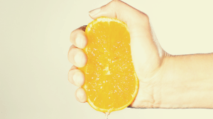 a hand squeezing an orange