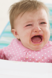 crying baby in a high chair