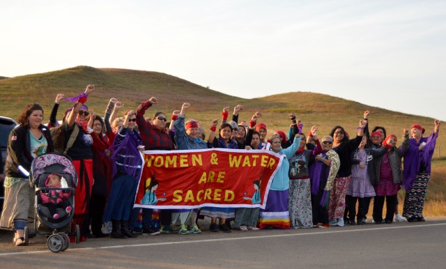"""September 22, 2015-Women from tribal coalitions stand united on the front line at the entrance of the Sacred Stone Camp to tell the world """"Water & Women Are Sacred."""" The coalitions came together across Turtle Island-from the northern region of Alaska, across the United States from California to Maine, and along the southern border of New Mexico and Oklahoma to support the Standing Rock Sioux Tribe. The tribal women's coalitions organized to increase safety for native women have member programs representing more than half of all federally recognized Indian Nations. (Photographer: Jacqueline """"Jax"""" Agtuca)"""