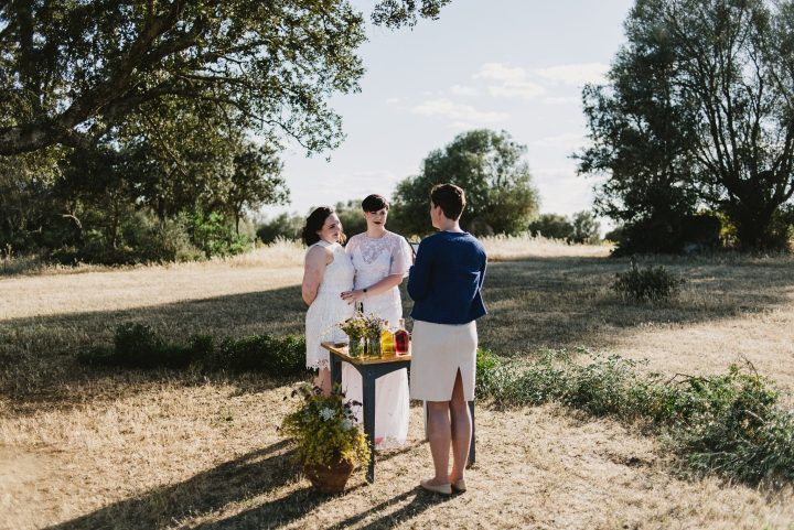 Two brides standing holding each other as they face their Alentejo wedding officiant during their ceremony. The bride on the left as a knee-length white dress and the bride on the right has a lace, floor-length dress. Both are wearing read heels and matching red lipstick. It is only the three of them with dried grass and trees around them.
