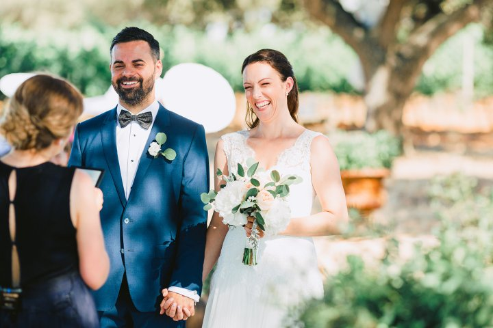 Bride and groom are laughing with happiness as they face their Alentejo wedding officiant. Bride is in a white, lace, capped sleeved gown and the groom is in a blue suit with black bow tie. In the background are trees and greenery.