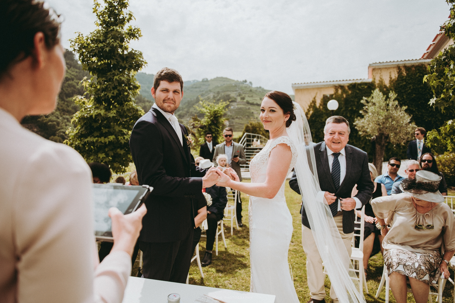 Bride and groom holding each other's hands as they look at their Douro Valley wedding celebrant with trees and rolling vineyards in the background.