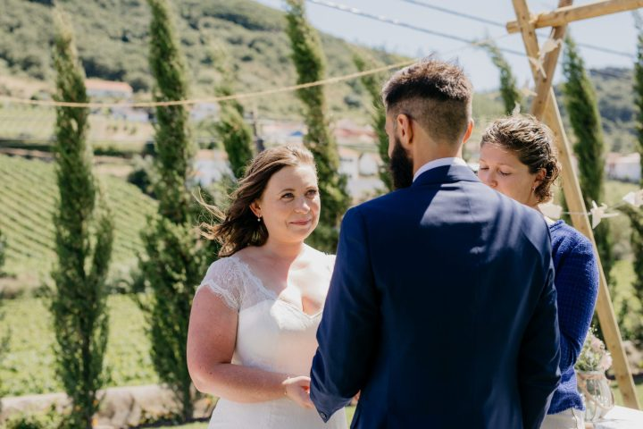 Torres Vedras wedding officiant  conducting a symbolical wedding ceremony in front of a bride and groom as the bride looks lovingly to her groom.Vineyards and fields of green in the background.