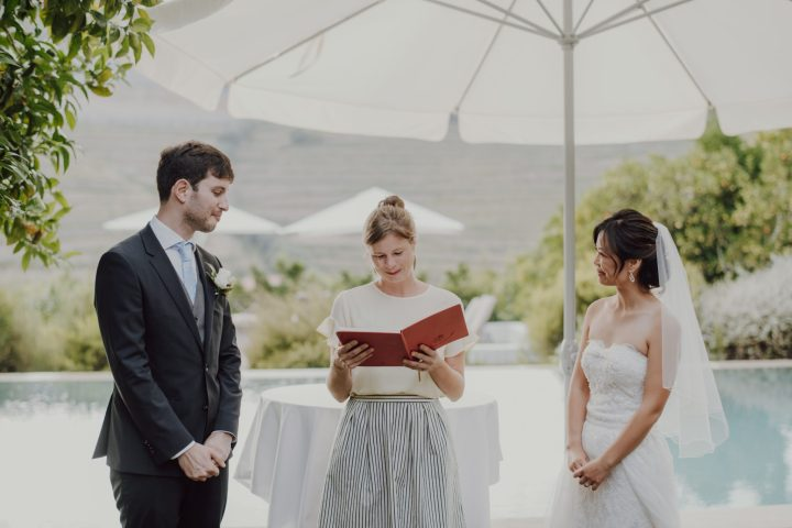 Douro Valley wedding officiant with a red book conducting a symbolical wedding ceremony in front of a bride and groom with the Douro Valley in the background.