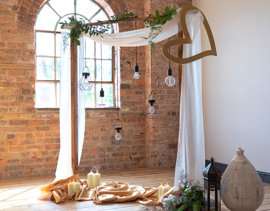 Dry Hire Wedding - Ceremony backdrop with draped voile hanging lights, wooden heart and lanterns