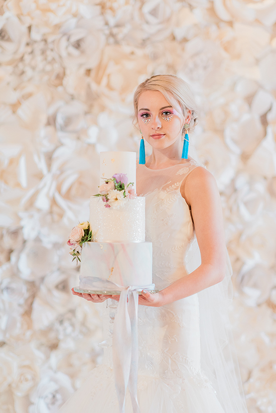 Bride with unicorn inspired wedding cake and flower wall