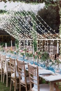 Fairy light installation over banquet tables in Walled Garden