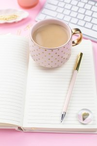 Tea in pretty pink cup with notebook and pen