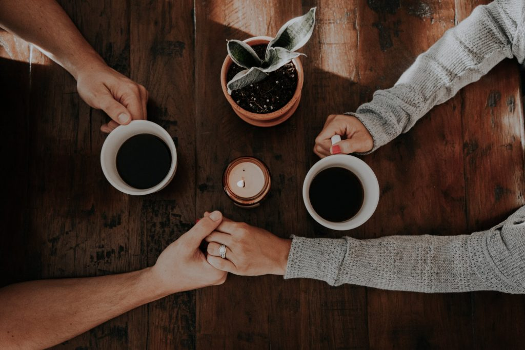 Couple holding hands drinking coffee