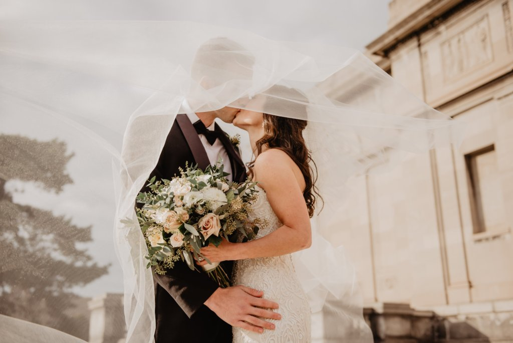 Couple Kissing Under a Veil - post covid wedding planning
