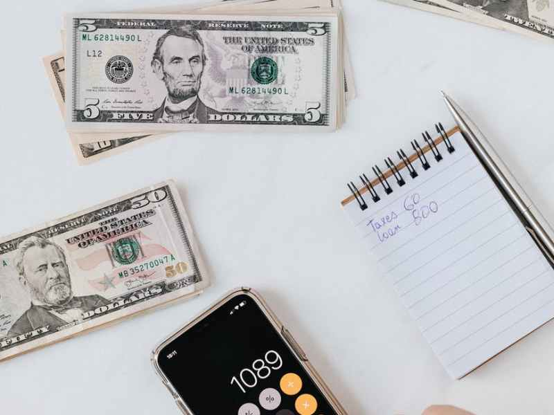 crop anonymous person calculating profit on smartphone calculator near banknotes
