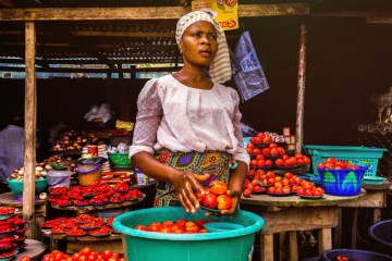 african woman holding tomatoes