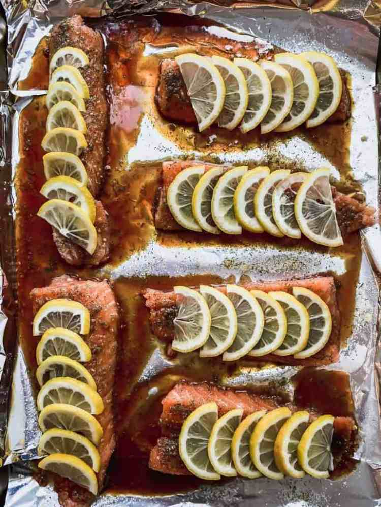 6 fillets with seasonings, sauce, and lemon slices on a foil lined sheet pan.