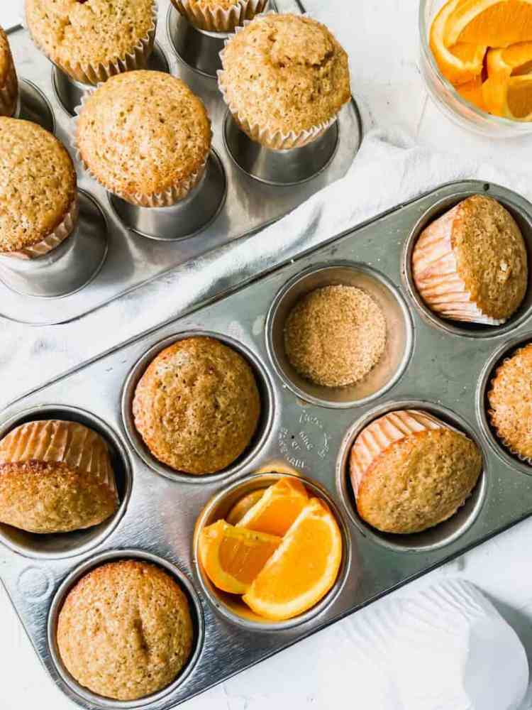 spiced orange muffins in muffin pans with coarse sugar and orange slices