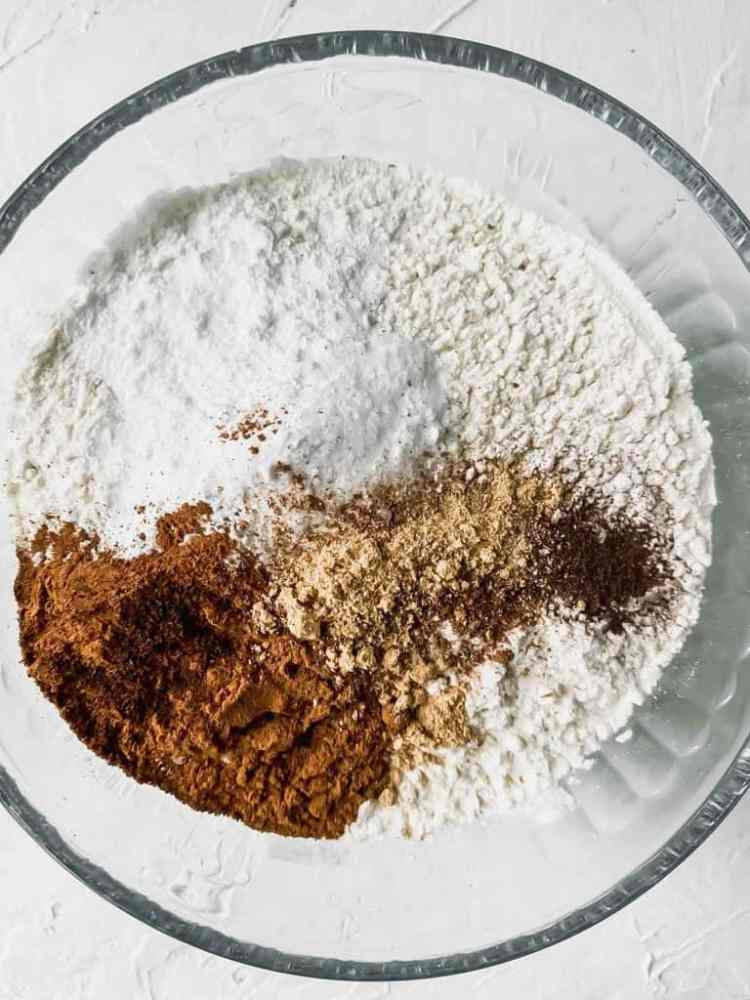 Dry ingredients for spiced orange muffins in a glass mixing bowl.